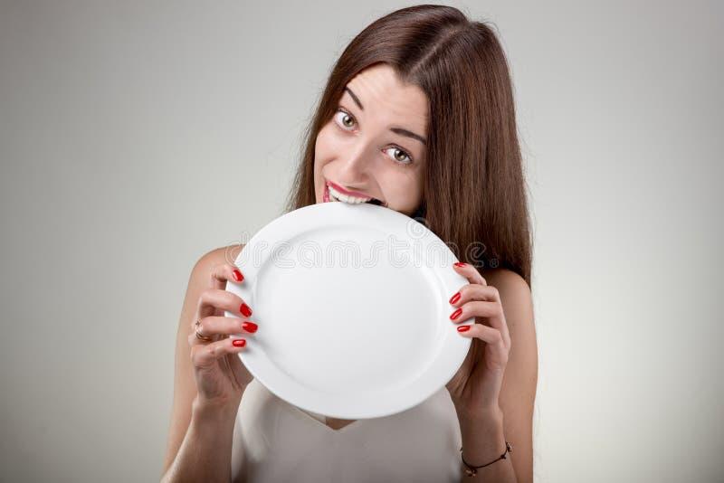 Η νέα γυναίκα δαγκώνει το κενό πιάτο στοκ εικόνα με δικαίωμα ελεύθερης χρήσης