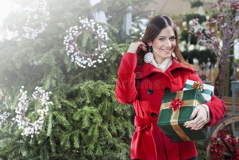 Η νέα γυναίκα αγοράζει τα δώρα Χριστουγέννων στοκ φωτογραφία