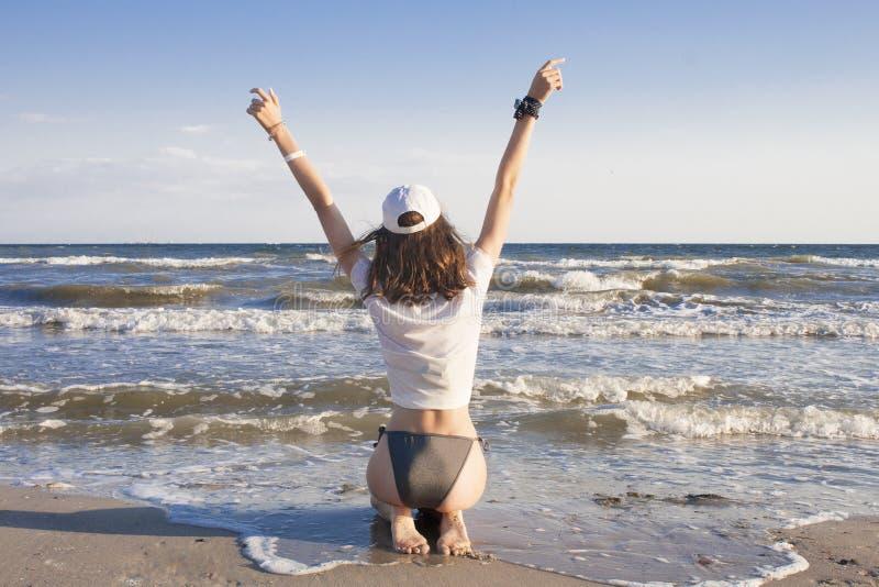 Η νέα γυναίκα αισθάνεται ευτυχής και ελευθερία, που χαλαρώνει, καθμένος στην άμμο, εν πλω στοκ εικόνες