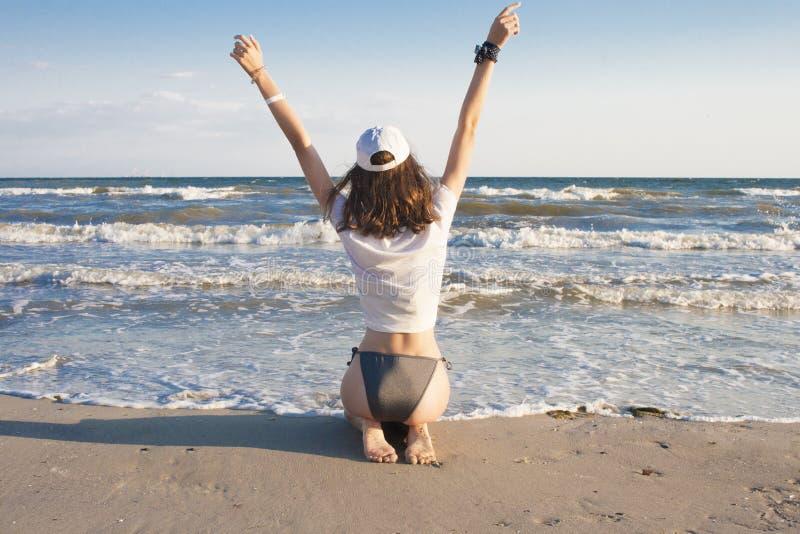 Η νέα γυναίκα αισθάνεται ευτυχής και ελευθερία, που χαλαρώνει, καθμένος στην άμμο, εν πλω στοκ φωτογραφία