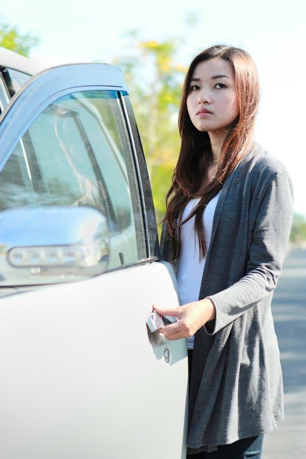 Η νέα γυναίκα ανοίγει την πόρτα αυτοκινήτων στοκ φωτογραφίες