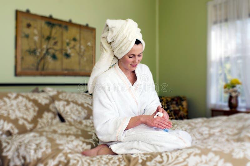 Η νέα γυναίκα απευθύνεται moisturiser στο δέρμα της στοκ φωτογραφίες