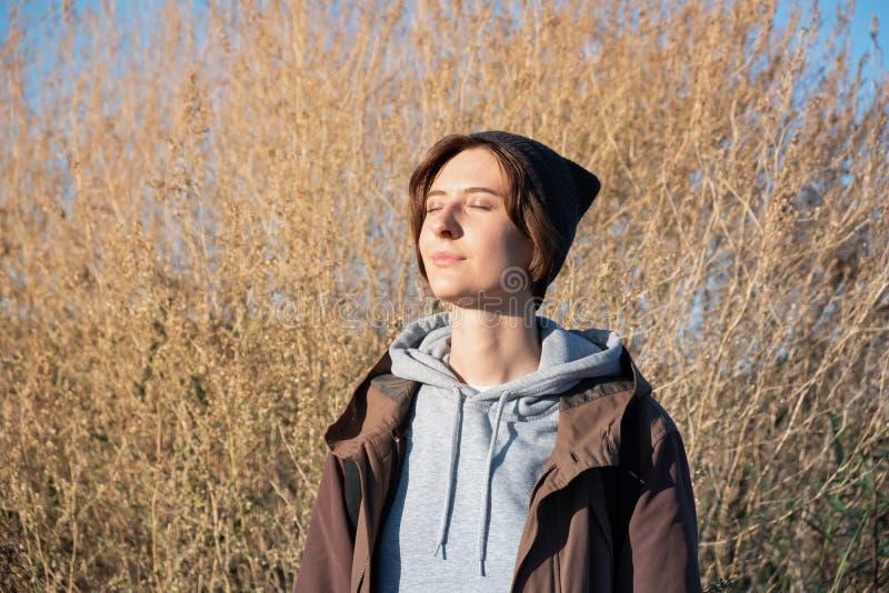 Η νέα γυναίκα απολαμβάνει τον ήλιο φθινοπώρου Θηλυκό στη ζακέτα υπαίθρια στο β στοκ εικόνα με δικαίωμα ελεύθερης χρήσης