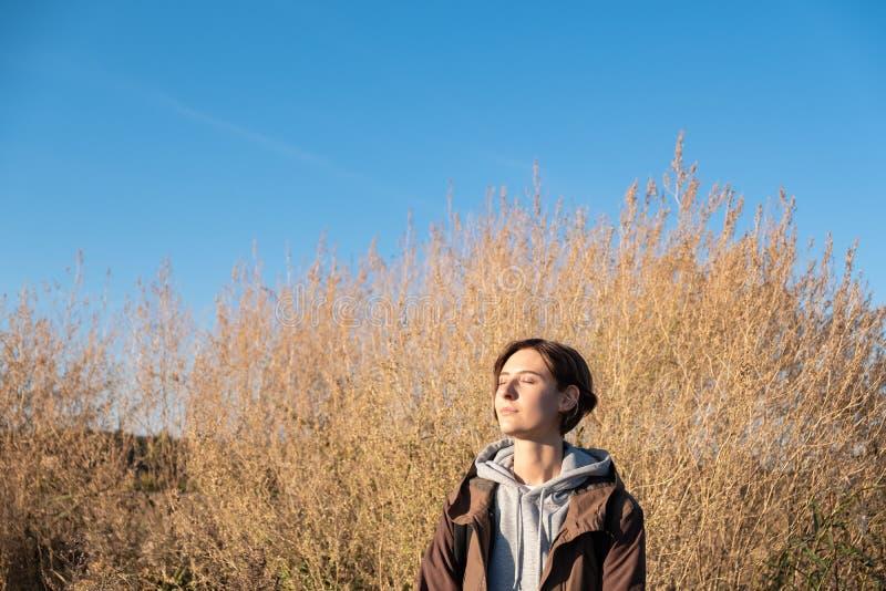 Η νέα γυναίκα απολαμβάνει τον ήλιο φθινοπώρου Θηλυκό στη ζακέτα υπαίθρια στο α στοκ εικόνες