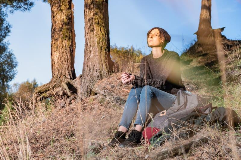 Η νέα γυναίκα απολαμβάνει το λεπτό καιρό φθινοπώρου Ο θηλυκός οδοιπόρος κάθεται κάτω στοκ εικόνα με δικαίωμα ελεύθερης χρήσης