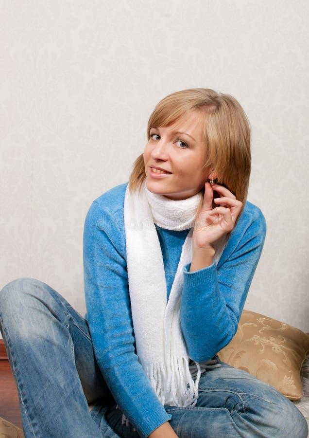Η νέα γυναίκα βάζει στο σκουλαρίκι στοκ φωτογραφία με δικαίωμα ελεύθερης χρήσης