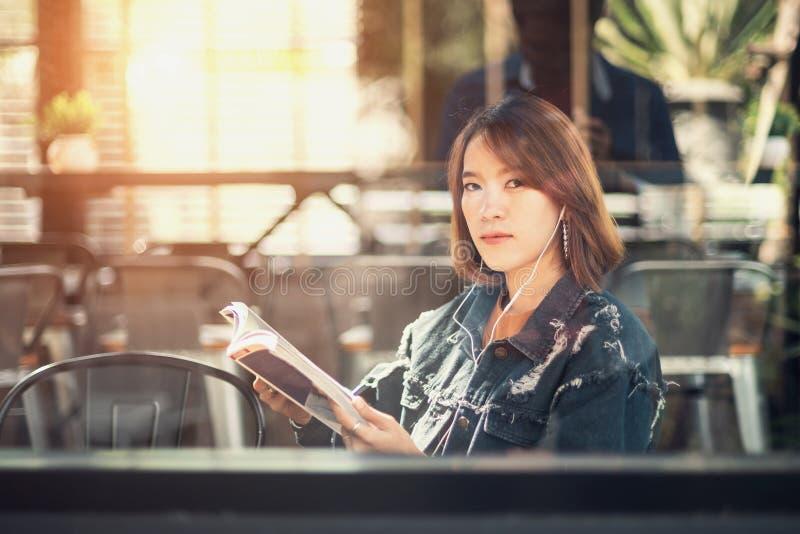 Η νέα γυναίκα διαβάζει και ακούει τη μουσική στοκ εικόνες