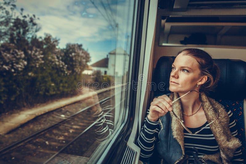 Η νέα γυναίκα είναι στο τραίνο και τα ρολόγια μέσω του παραθύρου ο στοκ φωτογραφία με δικαίωμα ελεύθερης χρήσης