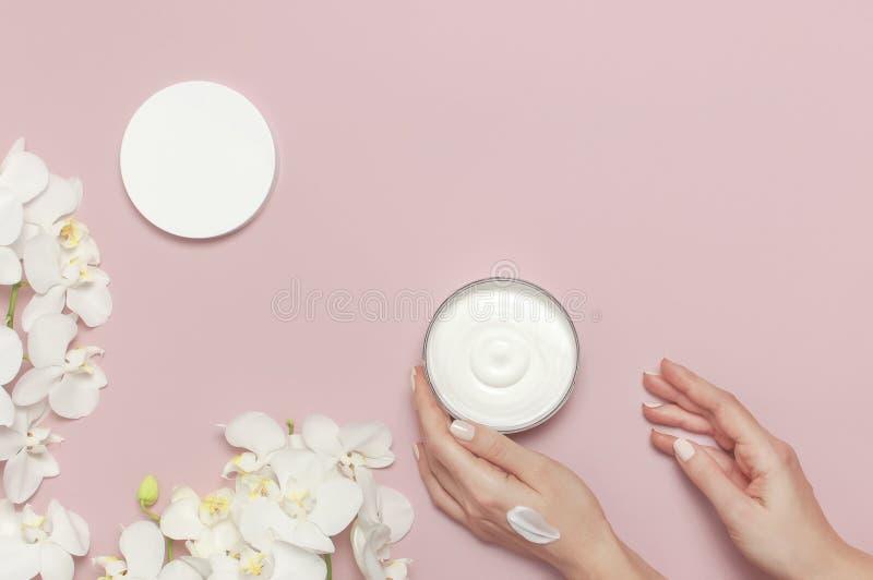 Η νέα γυναίκα ενυδατώνει το χέρι της με το καλλυντικό ανοιγμένο λοσιόν εμπορευματοκιβώτιο κρέμας με την άσπρη ορχιδέα Phalaenopsi στοκ εικόνα με δικαίωμα ελεύθερης χρήσης