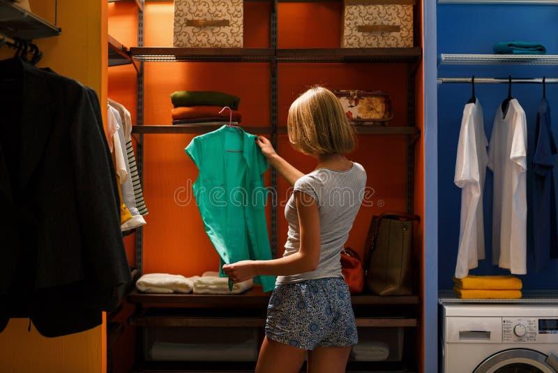 Η νέα γυναίκα επιλέγει τα ενδύματα στην ντουλάπα στοκ εικόνα