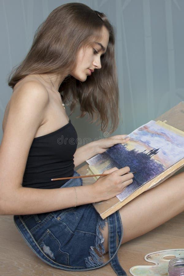 Η νέα γυναίκα επισύρει την προσοχή μια ζωγραφική watercolor σε χαρτί Ο θηλυκός καλλιτέχνης χρωματίζει watercolour το τοπίο στοκ φωτογραφίες