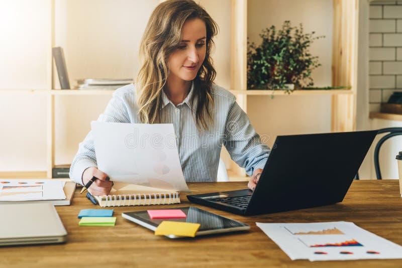Η νέα γυναίκα επιχειρηματιών κάθεται στον πίνακα κουζινών και χρησιμοποιεί το lap-top, εργασία, μελέτη Στον υπολογιστή επιτραπέζι στοκ φωτογραφία με δικαίωμα ελεύθερης χρήσης