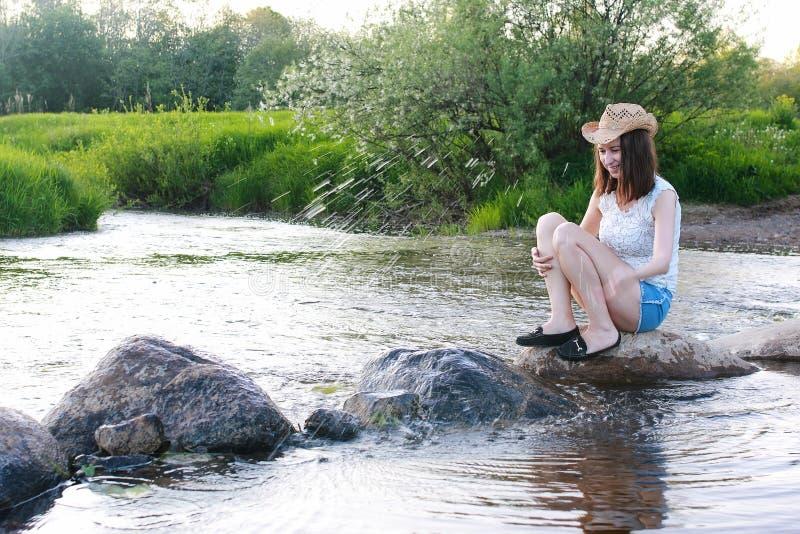 Η νέα γυναίκα θαυμάζει το ηλιοβασίλεμα εξισώνοντας την άνοιξη στο rive στοκ εικόνες