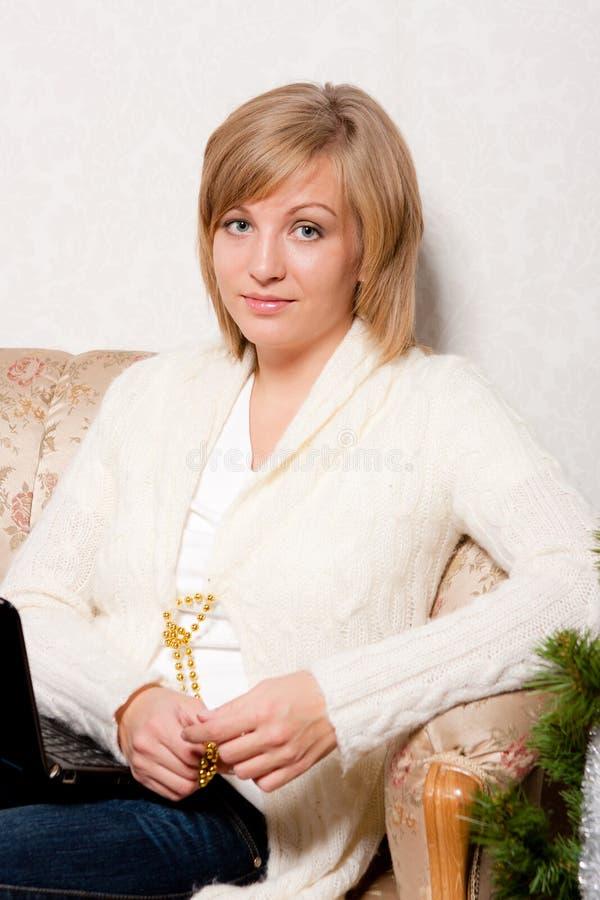 Η νέα γυναίκα κάθεται σε έναν καναπέ στοκ φωτογραφία με δικαίωμα ελεύθερης χρήσης