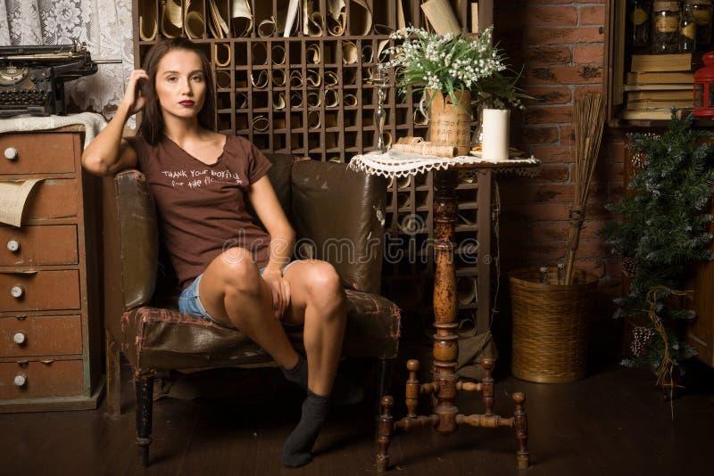 Η νέα γυναίκα κάθεται σε μια πολυθρόνα στοκ φωτογραφίες με δικαίωμα ελεύθερης χρήσης
