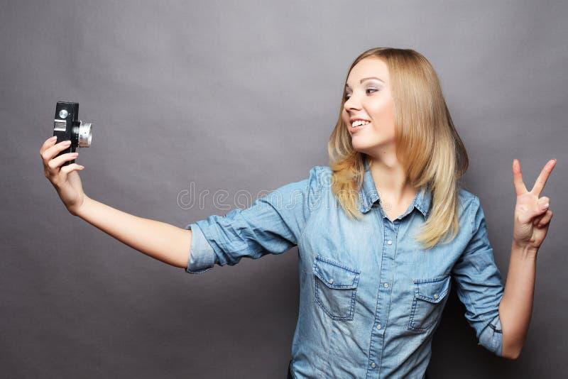 Η νέα γυναίκα κάνει selfie τη φωτογραφία με τη κάμερα στοκ φωτογραφία
