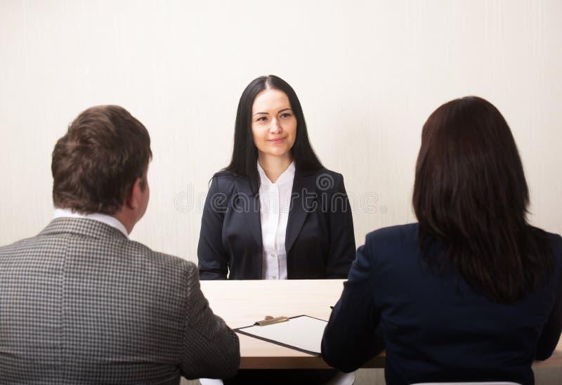 Η νέα γυναίκα κατά τη διάρκεια της συνέντευξης εργασίας και τα μέλη στοκ εικόνα