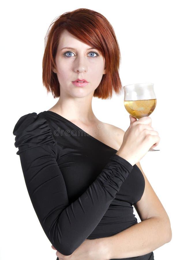 Η νέα γυναίκα κοιτάζει επίμονα το κράτημα του ποτηριού κρασιού της στοκ εικόνες