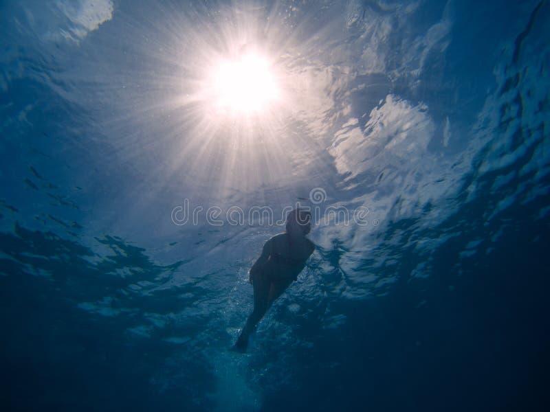 Η νέα γυναίκα κολυμπά με αναπνευτήρα στο σαφές μπλε νερό εικόνα από κάτω από στοκ φωτογραφία