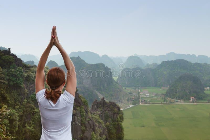 Η νέα γυναίκα κρατά ήρεμος και meditates εν ενεργεία τη γιόγκα στοκ εικόνα