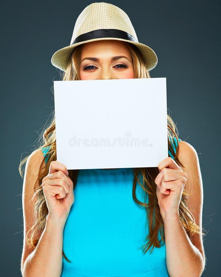 Η νέα γυναίκα κρύβει το πρόσωπό του πίσω από ένα έμβλημα στοκ φωτογραφίες