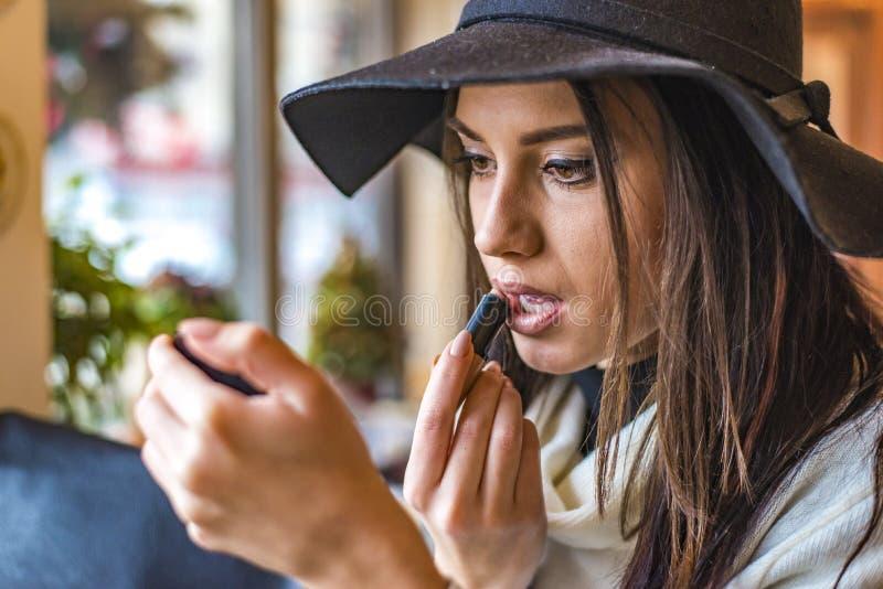 Η νέα γυναίκα με ένα καπέλο βάζει το κραγιόν στα χείλια στοκ εικόνες