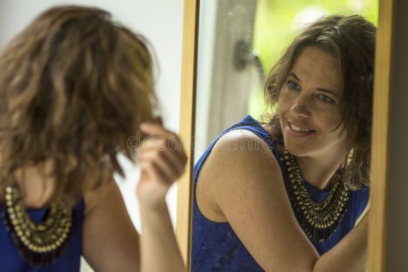 Η νέα γυναίκα με ένα χαμόγελο κοιτάζει στον καθρέφτη Ευτυχής στοκ φωτογραφίες με δικαίωμα ελεύθερης χρήσης