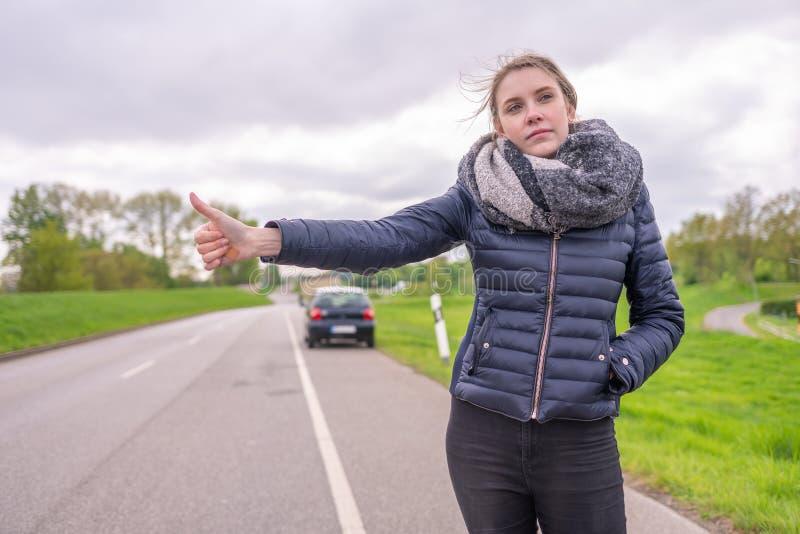 Η νέα γυναίκα με μια διακοπή αυτοκινήτων θέλει να κάνει ωτοστόπ στοκ εικόνες