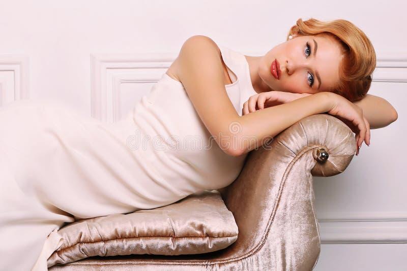 Η νέα γυναίκα με τα ξανθά μαλλιά στο αναδρομικό ύφος, φορά το κομψό άσπρο φόρεμα στοκ εικόνες