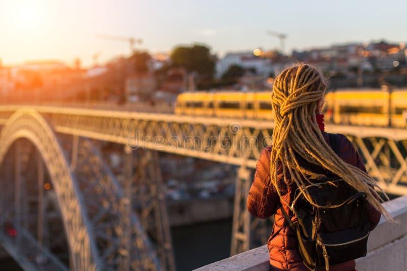 Η νέα γυναίκα με τα dreadlocks συναντά το ηλιοβασίλεμα στην πλατφόρμα εξέτασης απέναντι από τα DOM Luis Ι γέφυρα πέρα από τον ποτ στοκ φωτογραφία