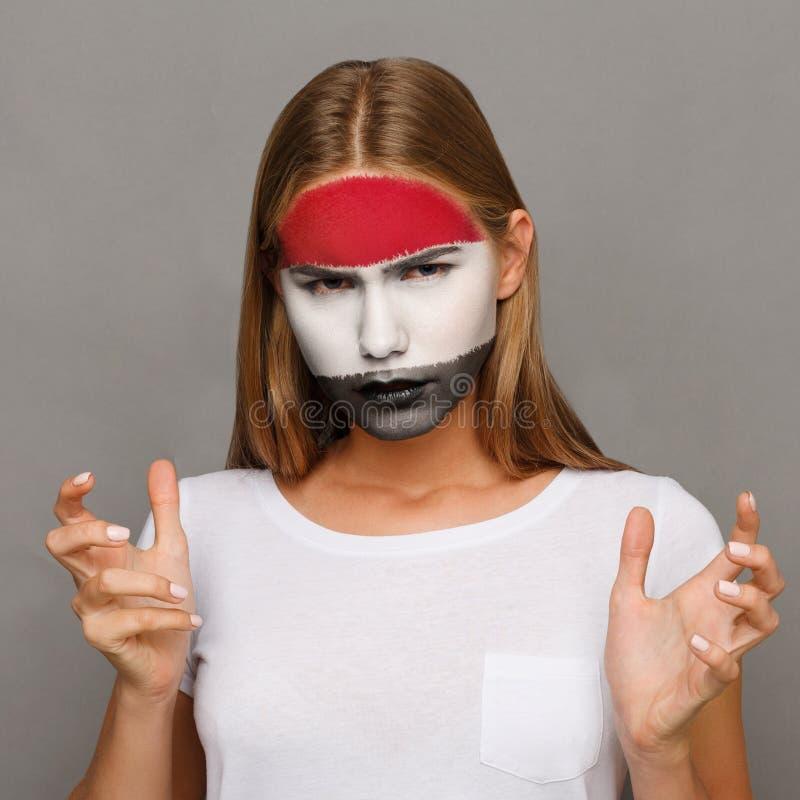 Η νέα γυναίκα με τη σημαία της Αιγύπτου χρωμάτισε στο πρόσωπό της στοκ εικόνα με δικαίωμα ελεύθερης χρήσης