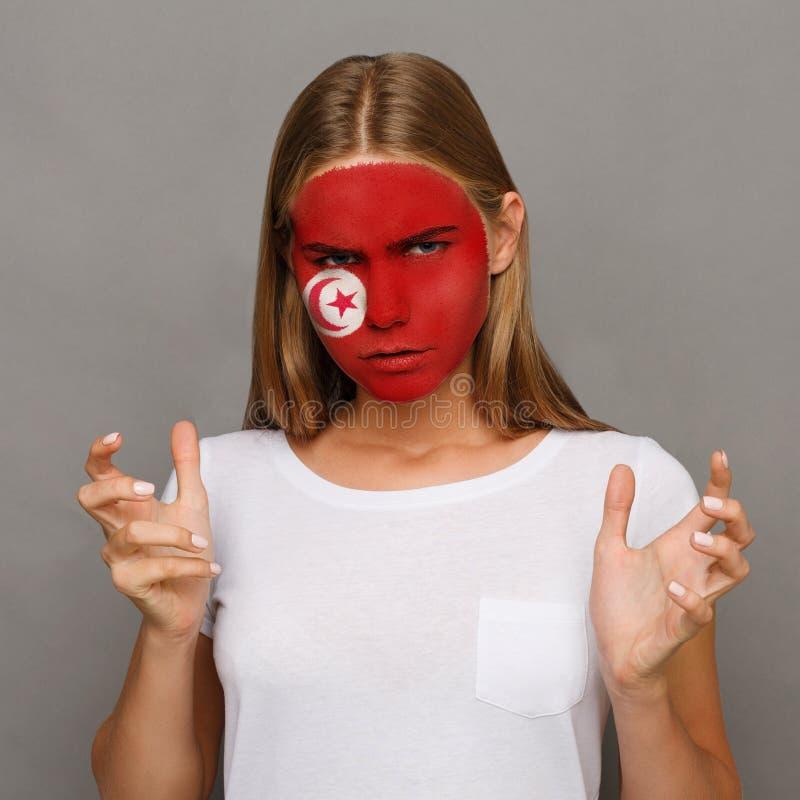 Η νέα γυναίκα με τη σημαία της Τυνησίας χρωμάτισε στο πρόσωπό της στοκ φωτογραφία