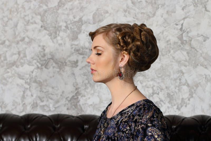 Η νέα γυναίκα με το hairdo και τις ιδιαίτερες προσοχές θέτει στον καναπέ στοκ εικόνα με δικαίωμα ελεύθερης χρήσης