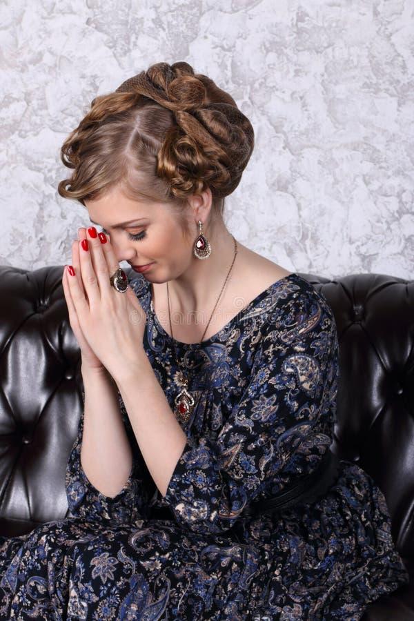 Η νέα γυναίκα με το hairdo προσεύχεται με το κλείσιμο των ματιών στον καναπέ στοκ εικόνες με δικαίωμα ελεύθερης χρήσης