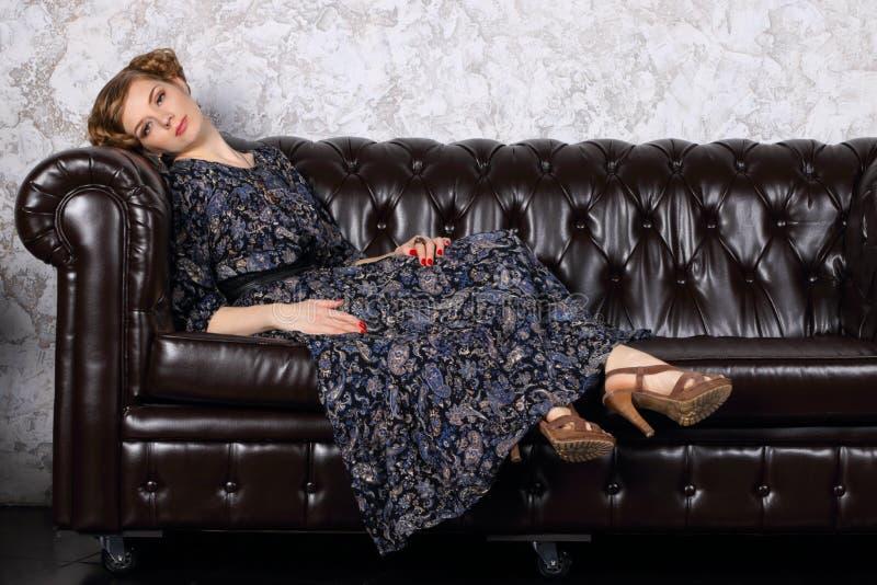 Η νέα γυναίκα με το hairdo στο φόρεμα βρίσκεται στο μαύρο καναπέ δέρματος στοκ φωτογραφίες