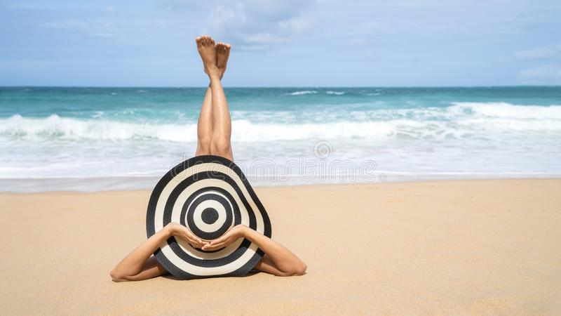 Η νέα γυναίκα μόδας χαλαρώνει στην παραλία Ευτυχής τρόπος ζωής νησιών Άσπρη άμμος, μπλε νεφελώδεις ουρανός και θάλασσα κρυστάλλου στοκ εικόνα