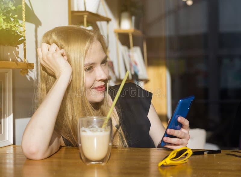 η νέα γυναίκα ομορφιάς πίνει τον καφέ και καλεί το τηλέφωνο, κορίτσι χρησιμοποιώντας το smartphone, οθόνη αφής, ευτυχές τρελλό πρ στοκ φωτογραφίες με δικαίωμα ελεύθερης χρήσης