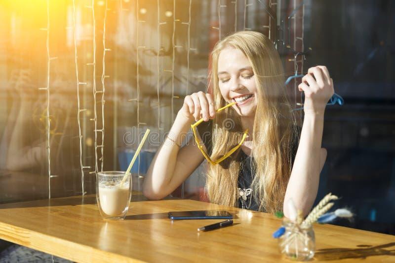 Η νέα γυναίκα ομορφιάς πίνει τον καφέ και καλεί το τηλέφωνο, κορίτσι χρησιμοποιώντας το smartphone, ευτυχές τρελλό πρόσωπο, αστεί στοκ εικόνες