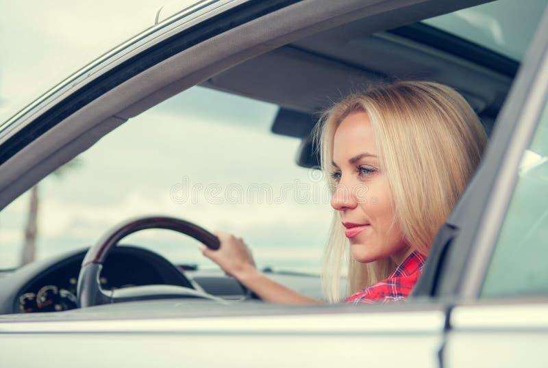 Η νέα γυναίκα οδηγεί ένα αυτοκίνητο στοκ εικόνα