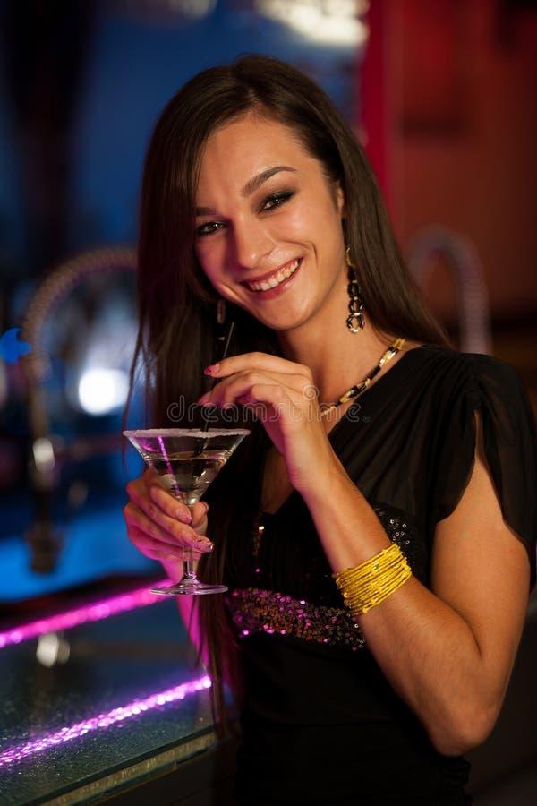 Η νέα γυναίκα πίνει ένα κοκτέιλ στη λέσχη νύχτας στοκ εικόνα