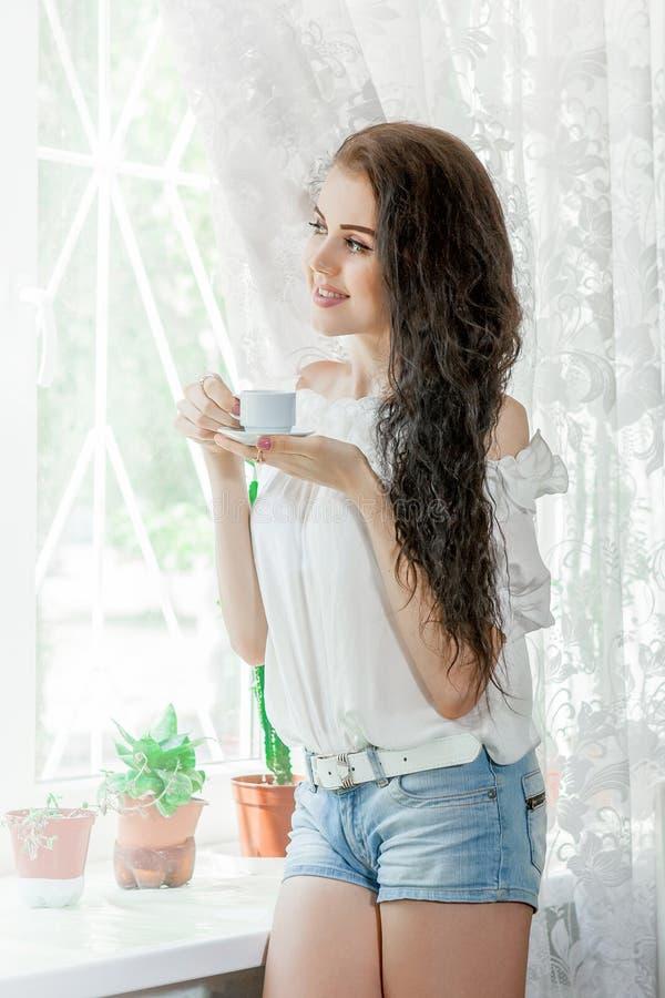 Η νέα γυναίκα πίνει τον καφέ στοκ φωτογραφίες με δικαίωμα ελεύθερης χρήσης