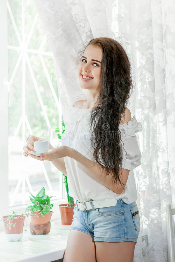 Η νέα γυναίκα πίνει τον καφέ στοκ φωτογραφία