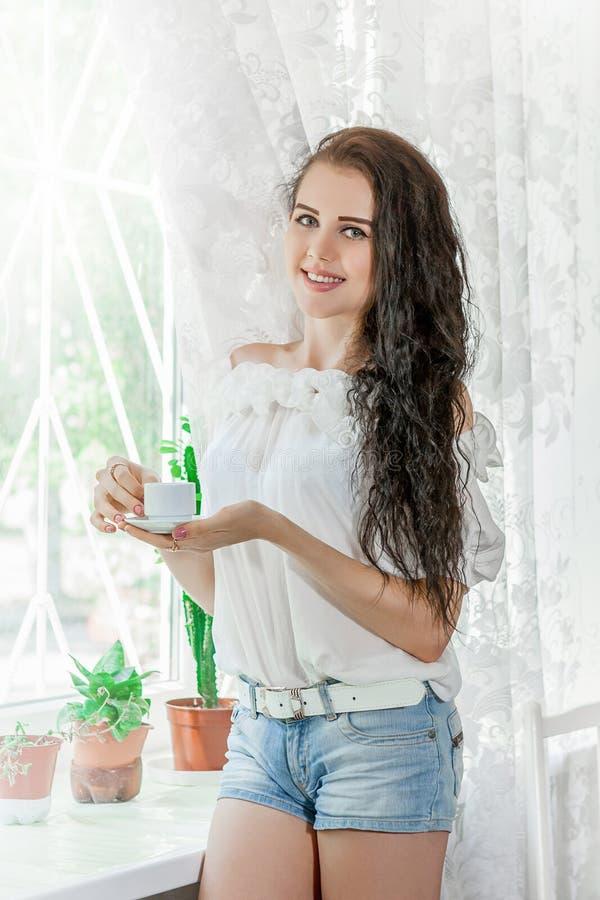 Η νέα γυναίκα πίνει τον καφέ στοκ εικόνα με δικαίωμα ελεύθερης χρήσης