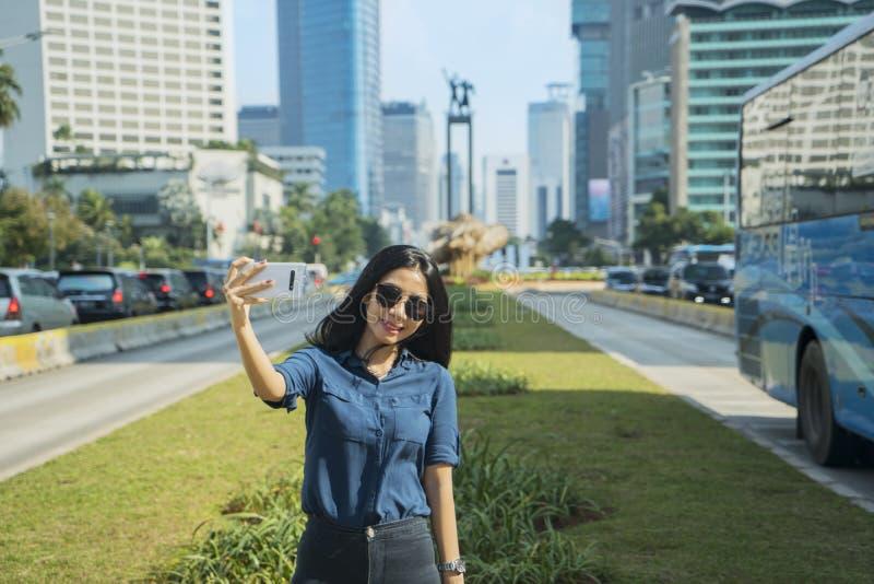 Η νέα γυναίκα παίρνει τη φωτογραφία με το ευπρόσδεκτο άγαλμα στοκ φωτογραφίες με δικαίωμα ελεύθερης χρήσης