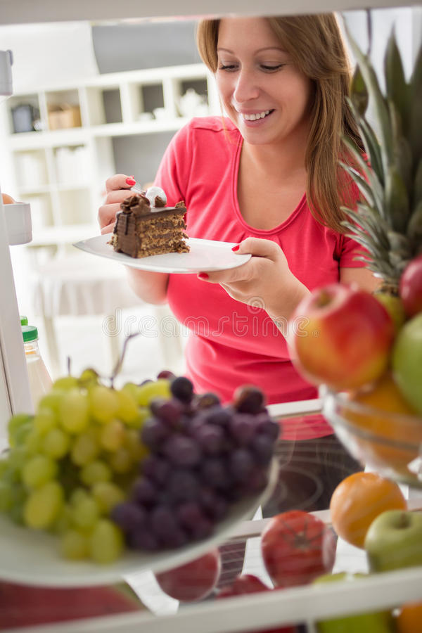 Η νέα γυναίκα παίρνει το κομμάτι του κέικ σοκολάτας από το ψυγείο στοκ εικόνα