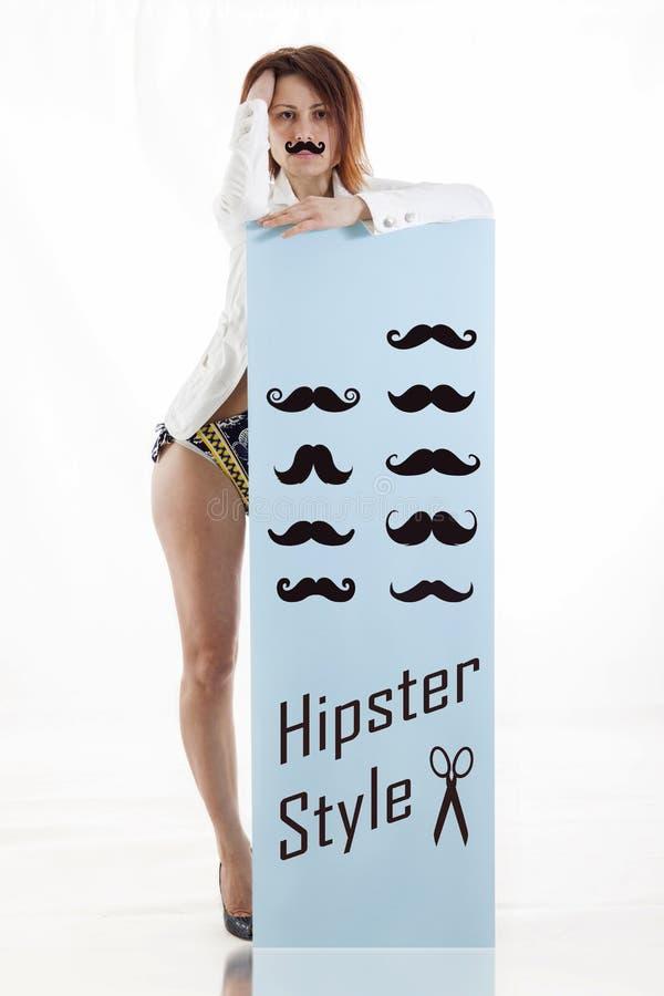 Η νέα γυναίκα παρουσιάζει μια επιτροπή με ένα σύνολο mustaches στοκ εικόνα με δικαίωμα ελεύθερης χρήσης