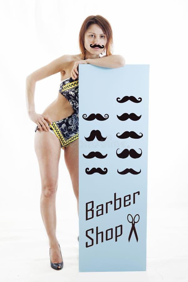 Η νέα γυναίκα παρουσιάζει μια επιτροπή με ένα σύνολο mustaches στοκ εικόνες