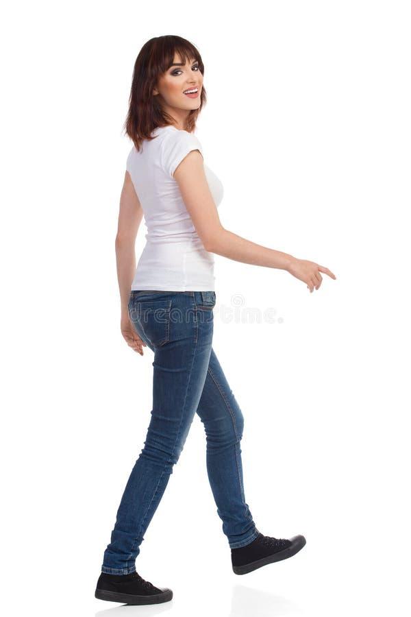 Η νέα γυναίκα περπατά και εξετάζει τη κάμερα πέρα από τον ώμο στοκ φωτογραφία με δικαίωμα ελεύθερης χρήσης