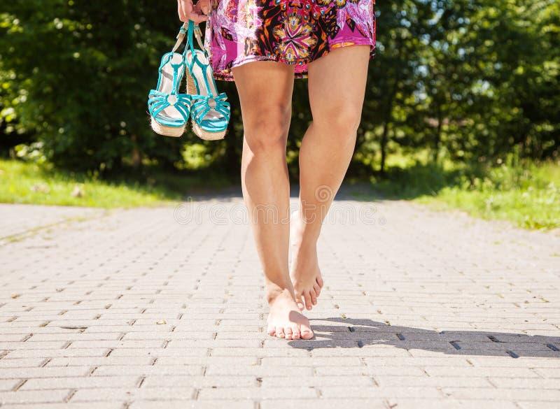 Η νέα γυναίκα πηγαίνει χωρίς παπούτσια στο πεζοδρόμιο στοκ φωτογραφία με δικαίωμα ελεύθερης χρήσης