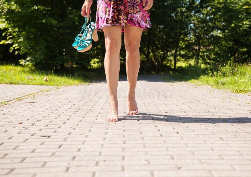 Η νέα γυναίκα πηγαίνει χωρίς παπούτσια στο πεζοδρόμιο στοκ φωτογραφίες